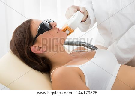 Close-up Of Smiling Young Woman Having Laser Treatment At Beauty Clinic On Face