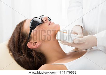 Close-up Of A Therapist Giving Laser Epilation Treatment On Women's Neck
