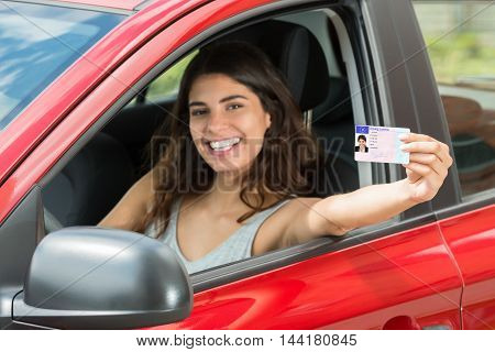 Smiling Young Woman Showing Her Driving License From Open Car Window