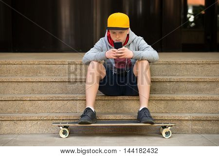 Boy Wearing Cap Sitting On Staircase Looking At Cellphone