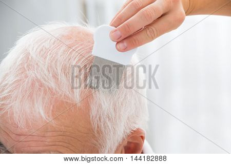 Close-up Of Doctor Doing Treatment On Senior Patient's Hair With Comb