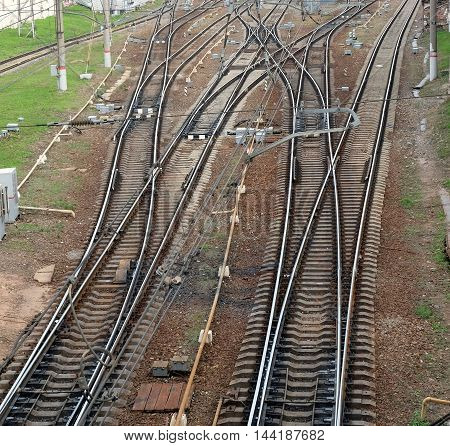 Industrial landscape with railroad tracks on concrete railway sleepers, arrows and track equipment top view
