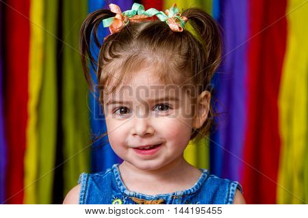 Portrait of an adorable girl with a great happy expression stands in front of a rainbow background. She has pig tails with ribbons.