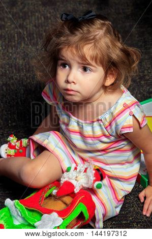 A young girl sits on a floor looking off to the distance inquisitively. She is playing with Christmas toys.