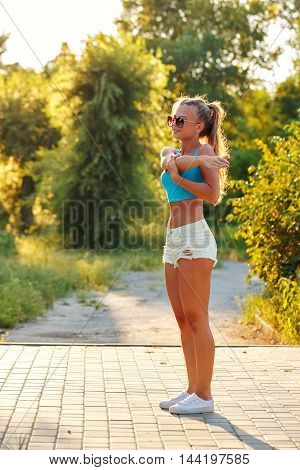 Young slim woman doing stretching of the shoulder girdle in a city park. Outdoors Sports. Healthy lifestyle concept. Morning exercises