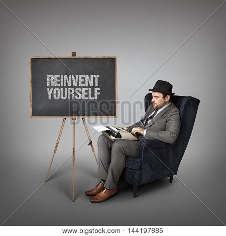 Reinvent yourself text on  blackboard with businessman and key