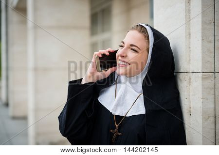 Young catholic nun calling phone - ouutside leaning at building