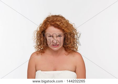 Hatred mature woman showing her disappointment in studio. Angry middle aged woman posing isolated on white background.