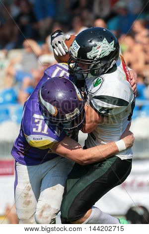 VIENNA, AUSTRIA - JULY 5, 2015: DB Gregor Mernyi (#31 Vikings) tackles WR Tobias Morgenbesser (#84 Dragons) in a game of the Austrian Football League.