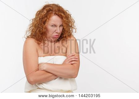 Portrait of disdaining mature or senior woman posing isolated on white background. Beautiful lady posing with her arms crossed or folded in studio.