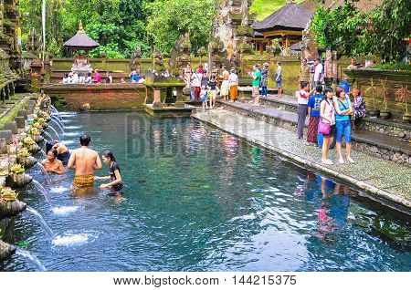 Bali,Indonesia-May 29,2010: Worshippers make an offering & many tourists visit at the Tirta Empul Temple on May 29,2010 in Bali, IndonesiaThey believe that water can bring good health and good luck.