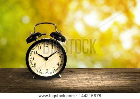 Alarm Clock On Wood With Blurry Shiny Bokeh In Background