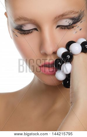 young woman holding black and white beads at mouth isolated on white