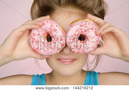 girl with two donuts on pink background