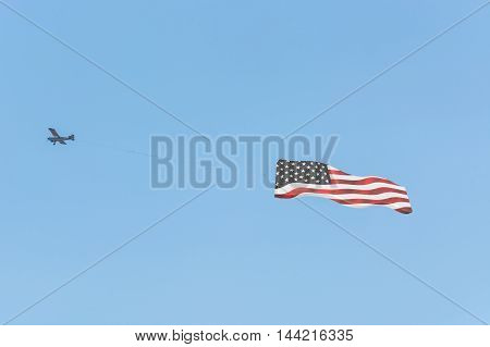 Banner towing small engine aircraft towing banners for advertising. Here the flag of America.