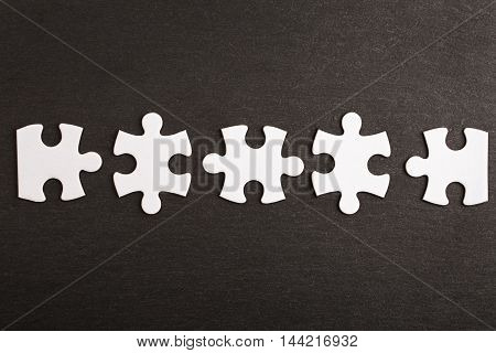 Incomplete puzzle on black surface. Business and teamwork concept.
