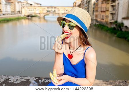 Young female tourist in the blue dress and hat eating cantuccini in Florence city. Cantuccini is traditional italian almond biscuits.