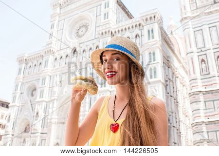 Young female traveler holding lampredotto sandwich in the center of Florence city. Lampredotto is a typical Florentine dish made from the stomach of a cow