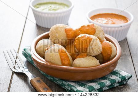 Canarian potatoes (papas arrugadas) with mojo sauce on wooden table