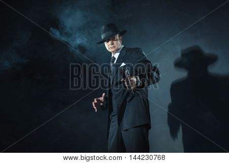 Vintage 1940 gangster shooting with a gun.