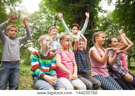 Group of positive children playing in the park sitting on the bench