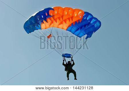 Paraglider flying on colorful parachute in blue clear sky at a bright sunny summer day. Active lifestyle extreme hobbies