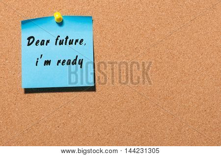 Hand writing Dear Future I'm ready on blue sheet of paper at notice board with empty space.