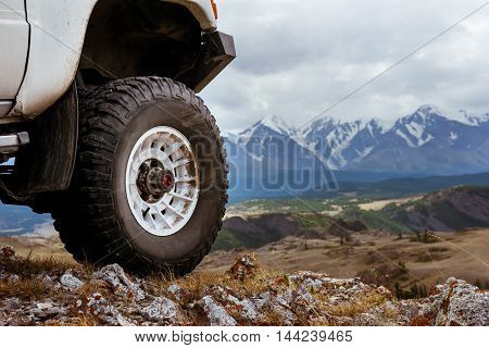 Big car wheel is standing on the rocks on mountain backdrop. Altay mountains, Siberia, Russia