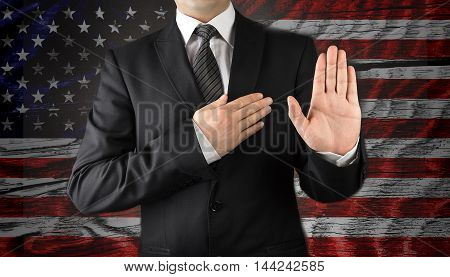 Men in suits taking oath in front of the American flag
