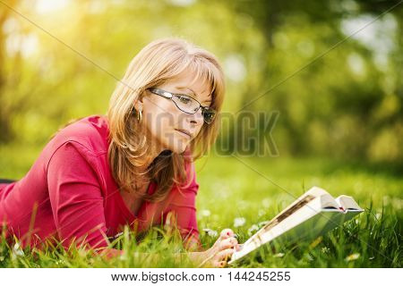 Woman reading outdoors.Happy woman reading a book during springtime in nature.