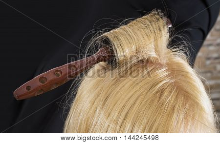 Hairbrush in blond long hair  isolated on black background