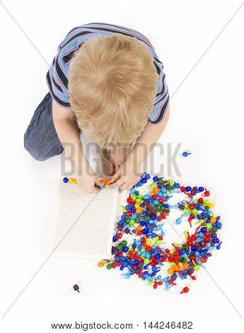 Child plays with a mosaic. Education concept