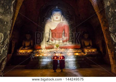 Bagan Myanmar November 13th 2014: Young monks praying in front of a statue of Buddha