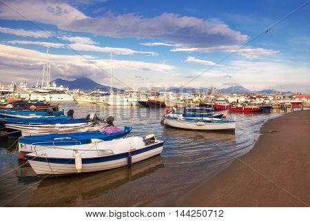 The beach in front of the marina of Naples with the sailboats and motorboats moored on the seashore. On background the volcano Vesuvius which characterizes the landscape of this city.