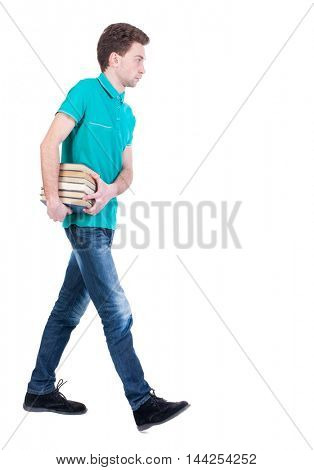 side view of going man carries a stack of books. Curly kid in a turquoise jacket carries books