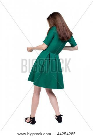 back view of standing girl pulling a rope from the top or cling to something. backside view of person. Isolated over white background. The slender brunette in a green short dress pulls the rope.