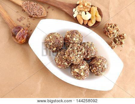 Indian sweet food dry fruits and nuts laddu, which is a traditional, healthy, nutritious and popular dish, is made from items like dates, raisins, almonds, cashew nuts and flaxseeds, in a tray.