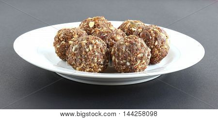 Indian sweet dry fruits and nuts laddu, which is a traditional, healthy, nutritious and popular dish, is made from items like dates, raisins, almonds, cashew nuts and flaxseeds, in a plate.