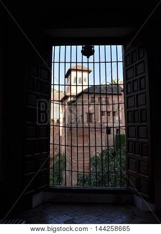 Vista de los alrededores de la alhambra a través de una ventana con rejillas.