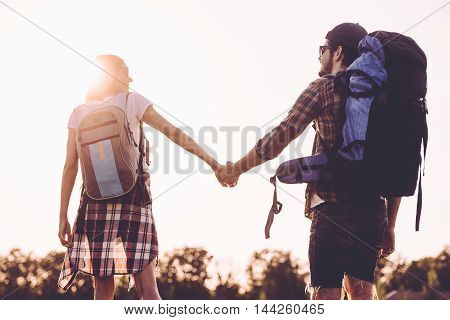 Discovering new horizons together. Rear view of young couple with backpacks walking together and holding hands