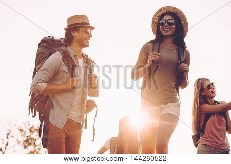 Nice day for hiking. Low angle view of young people with backpacks walking together and looking happy
