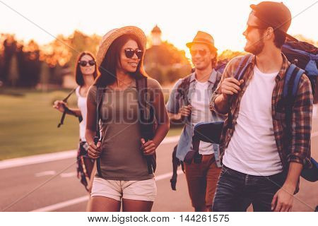 Having freedom to go anywhere. Group of young people with backpacks walking together by the road and looking happy