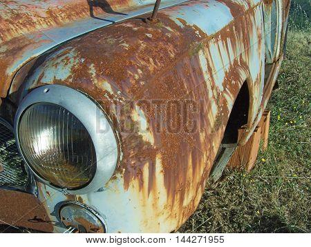 Old, vintage rusty car in a junkyard