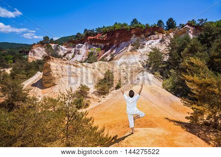 The elderly woman in special form of yoga  performs asana Tree. Orange and red picturesque hills in Roussillon