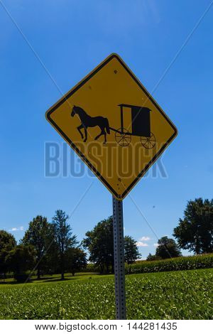 Kirkwood PA - August 23 2016: A yellow hazard sign alerts motorists of slow moving horse-drawn Amish buggies in Lancaster County.