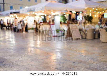 night or evening scene on street full of restaurant