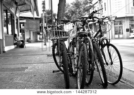 Honolulu Hawaii - August 6 2016: A row of locked bicycles on a sidewalk in downtown historic Chinatown.