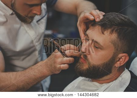 Serious Bearded Man Getting Beard Haircut With A Straight Razor By Barber While Sitting In Chair At Barbershop. Barbershop Theme