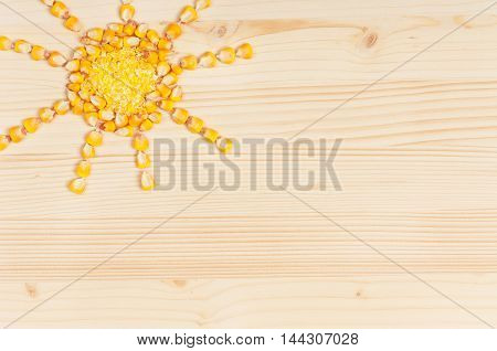 Abstract picture from grains of crude corn on a wooden surface