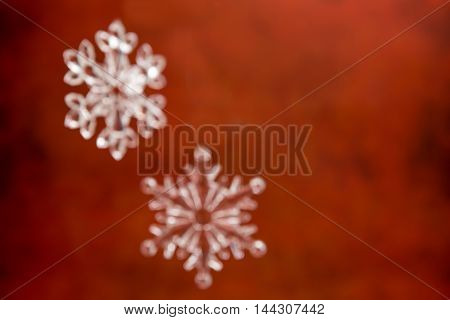 Closeup of de focused snowflakes over red background